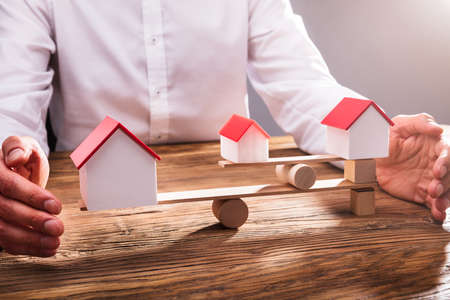 Close-up Of Businesspersons Hand Covering Balance Between House Model On Seesaw In Office