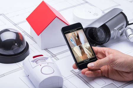 Architect Using Home Security System On Mobile Phone Near Security Equipments And House Model Фото со стока
