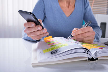 Close-up Of A Woman Using Mobile Phone With Diary On Desk