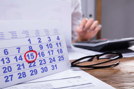 Close-up Of Calendar And Invoice In Front Of Businessperson Working At Workplace Фото со стока