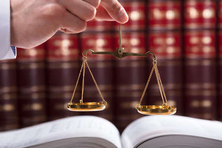 Judge Holding Justice Scale In Front Of Law Book