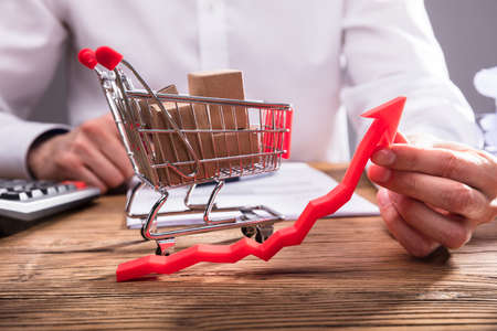 Businesspersons Hand Holding Arrow In Front Of Shopping Cart Full Of Cardboard Boxes