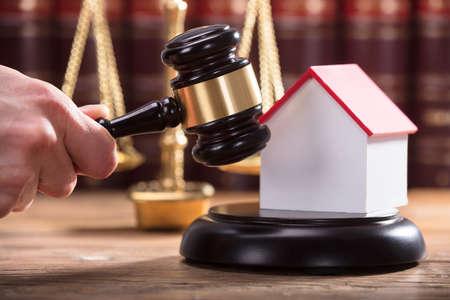 Judges Hand Striking Gavel Near House Model Фото со стока