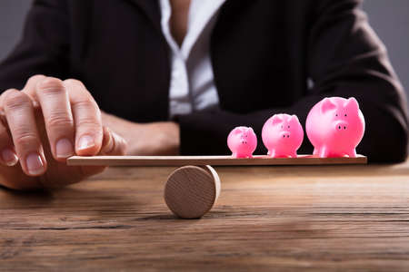 Businesspersons Finger Balancing Pink Piggybanks On Seesaw Over Wooden Desk
