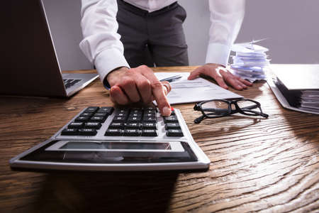 Businesspersons Hand Calculating Bill With Calculator On Wooden Desk