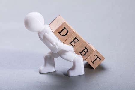 White Human Figurine Carrying Debt Wooden Blocks On Grey Background Фото со стока