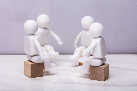 Four White Human Figurines Sitting On Wooden Block Having Meeting Together Stock Photo