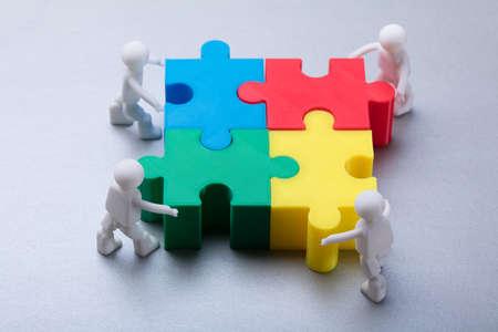 Human Figures Solving Multicolored Jigsaw Puzzle On Grey Background Foto de archivo