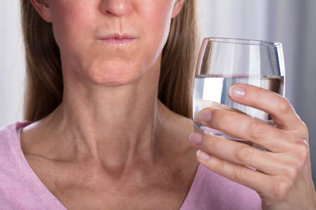 Close-up of woman rinçage et se gargariser avec de l'eau en verre