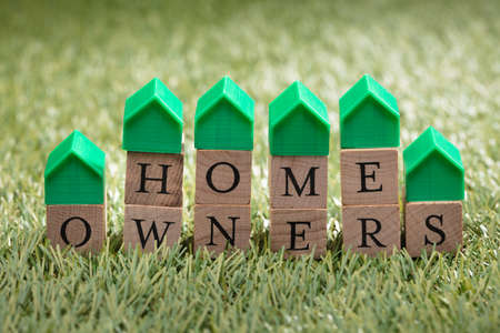 Miniature House Model Over Wooden Block Showing Home Owners Text On Green Grass Foto de archivo