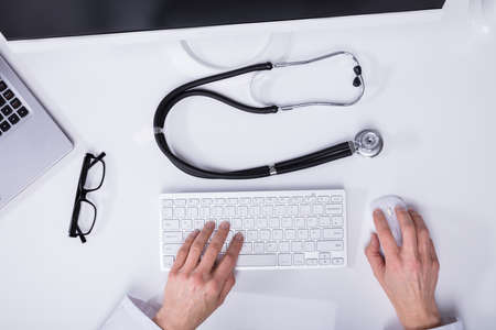 Elevated View Of A Doctors Hand Typing On Computer Keyboard With Stethoscope On Desk Фото со стока