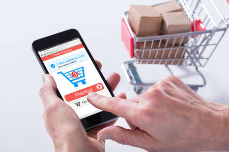 Close-up Of A Person Using Online Shopping Application On Mobile Phone With Cart