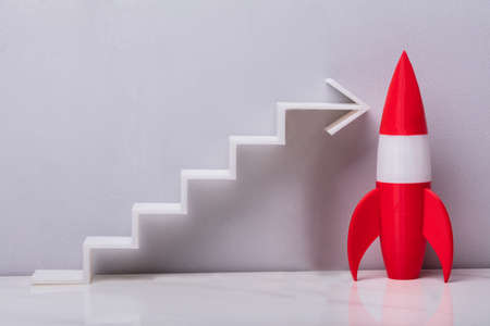 Red Rocket Near White Increasing Arrow Graph On Grey Background Фото со стока