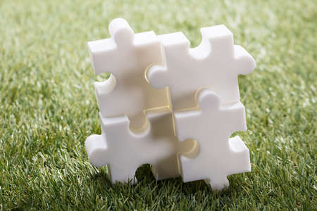 Elevated View Of Four White Jigsaw Puzzle On Green Grass