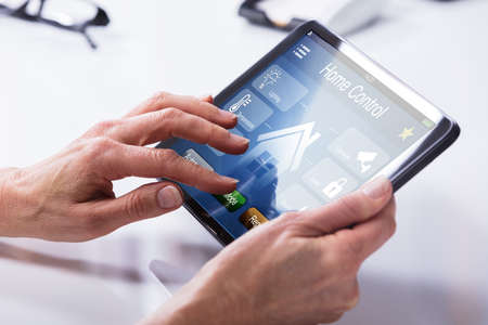 Close-up Of A Persons Hand Using Home Control System On Digital Tablet Фото со стока