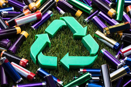 Elevated View Of Green Recycle Symbol Surrounded With Batteries
