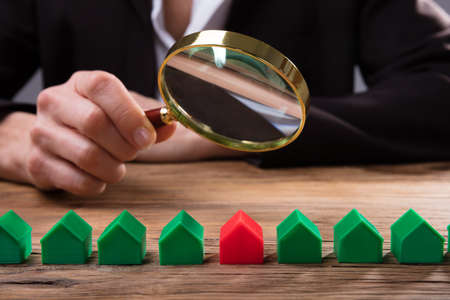 Businessperson's Hand Holding Magnifying Glass Over House Model Arranged In A Row