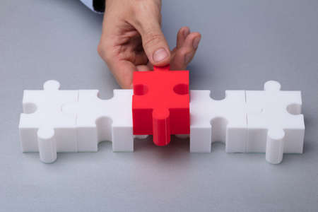 A Persons Hand Placing Red Piece Between White Jigsaw Puzzle Фото со стока