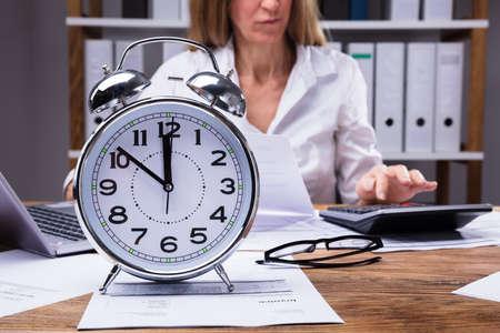 Close-up d'un réveil sur la facture en face de Businesswoman Working In Office