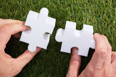 Close-up Of A Human Hand Holding Two White Jigsaw Puzzle On Green Grass Фото со стока