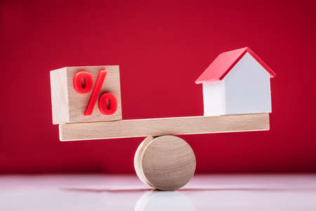Close-up Of Wooden Seesaw Showing Balance Between Percentage Symbol And House Model