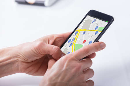 Close-up Of A Persons Hand Using GPS Navigation Map On Mobile Phone