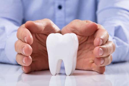 La mano del hombre que protege el diente blanco higiénico saludable sobre mesa reflectante