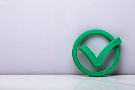 3d Green Check Mark Icon In Front Of Wall Stock Photo