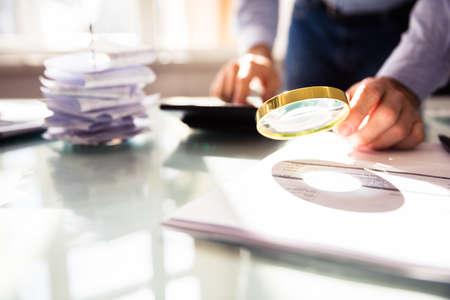 Mano de empresario analizando factura a través de una lupa Foto de archivo