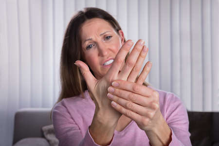 Close-up Of Upset Woman Suffering From Palm Pain At Home