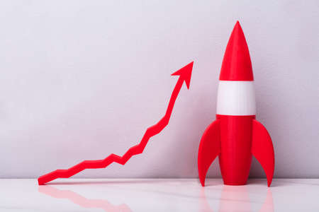 Red Rocket Near White Increasing Arrow Graph On Grey Background Stock Photo