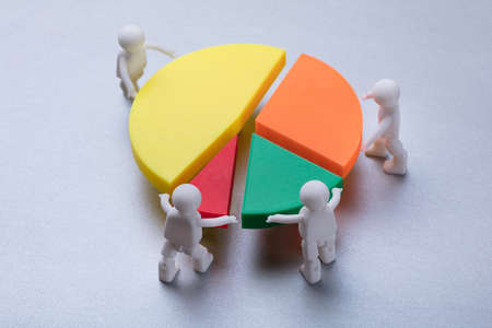 Elevated View Of Human Figures Connecting Pieces Of Multicolored Pie Chart On Grey Background