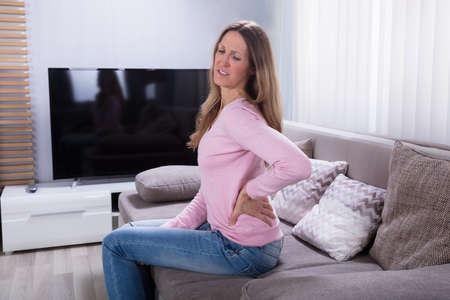 Mature Woman Sitting On Sofa Suffering From Backache At Home