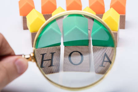 Green House Model Over Homeowner Association Wooden Blocks Seen Through A Person Holding Magnifying Glass