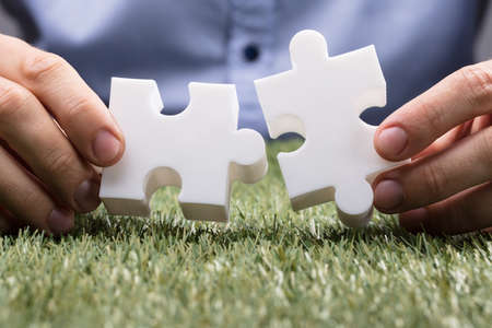 A Person's Hand Connecting Two White Jigsaw Puzzle Over Green Grass