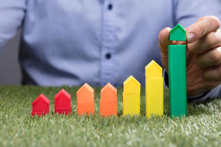 A Persons Hand Placing Miniature House Model Over Green Bar On Grass Stock Photo