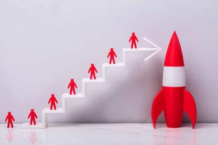 Rood menselijk beeldje dat zich op witte stijgende pijlgrafiek bevindt dichtbij rode raket Stockfoto
