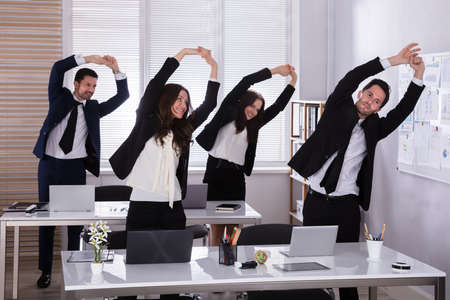 Empresarios felices haciendo ejercicio de estiramiento detrás del escritorio en el lugar de trabajo Foto de archivo