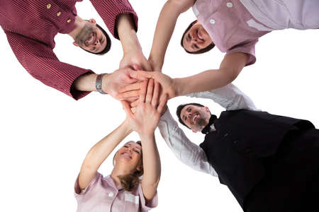 Low Section View Of Smiling Young Hotel Staff Stacking Their Hands Stock Photo