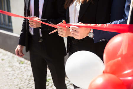 Close-up Of Businesspeople Hand Cutting Red Ribbon With Scissors Standard-Bild