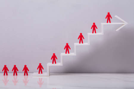 Red Human Figures Standing On Increasing White Arrow Graph In Front Grey Background