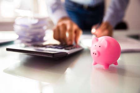 Close-up Of Pink Piggybank Near Businesspersons Hand Using Calculator 版權商用圖片