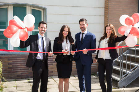 Happy Businesspeople Cutting Ribbon Outside Office Building