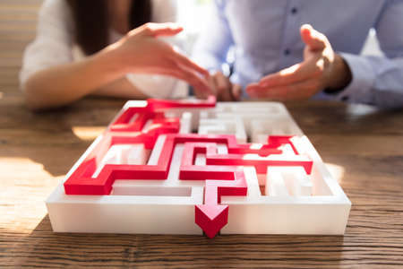 Close-up Of Maze Puzzle With Red Arrow In Front Of Businesspeople