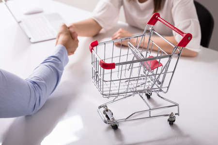 Close-up Of Empty Shopping Cart On Desk Near Two Businesspeople Shaking Hands