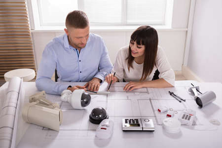 Two Architects Working On Blueprint With Security Equipments On Desk Stock Photo