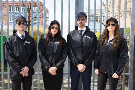 Retrato, de, hombres y mujeres jóvenes, guardias de seguridad, llevando, uniforme, y, anteojos Foto de archivo