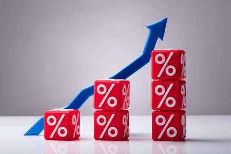 Aumentando i cubi rossi impilati con il simbolo di percentuale e la freccia blu che mostra la direzione verso l'alto Archivio Fotografico