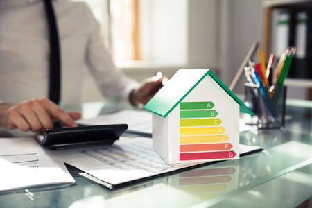 Close-up del modello di casa che mostra il tasso di efficienza energetica nella parte anteriore della mano dell'uomo d'affari utilizzando la calcolatrice