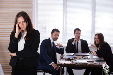 Porträt einer traurigen Geschäftsfrau vor ihren Kollegen, die im Amt sitzen Standard-Bild